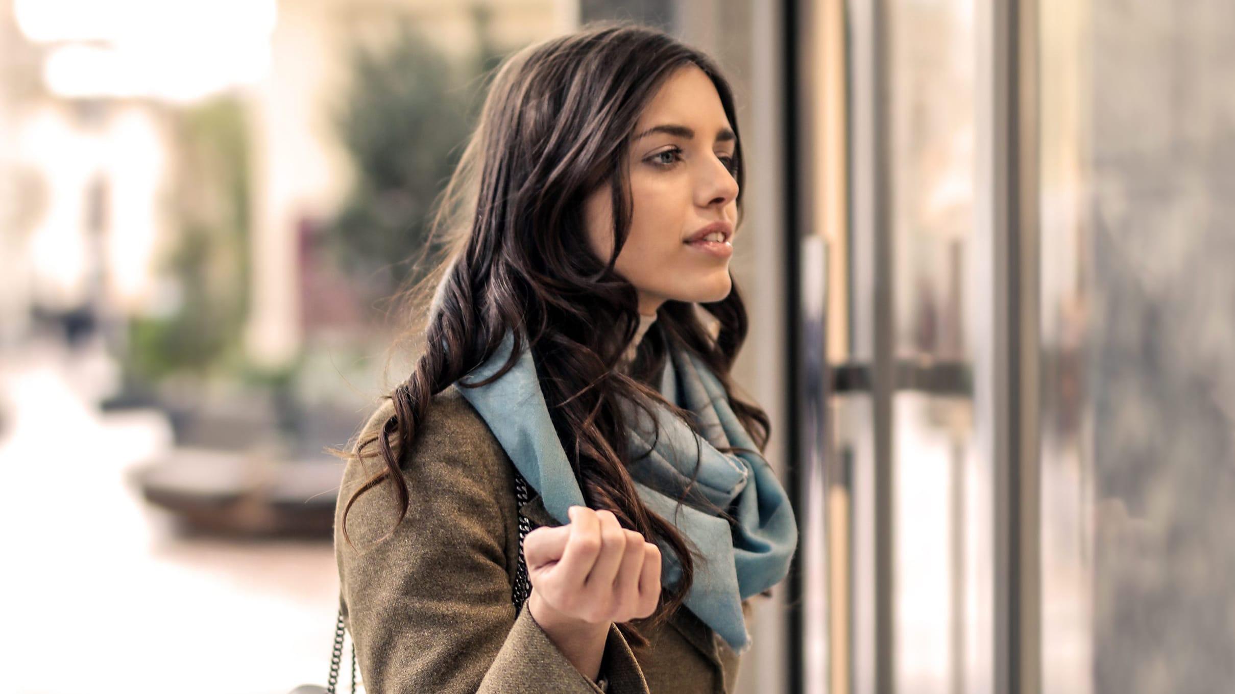 MOBILVERSION-Kvindelig brunette ser gennem et butiksvindue da hun har hørt musik fra forretningen